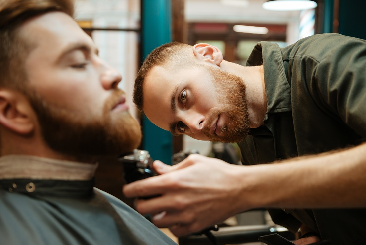 Barber trimming the full beard of a customer