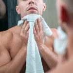 man drying face with towel before dry shaving with an electric shaver