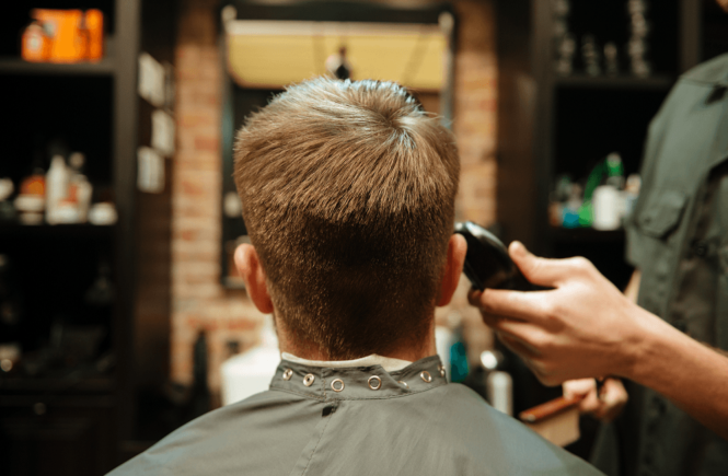 A barber trimming the hairs of his client with one of the best clippers for hair stylist salons