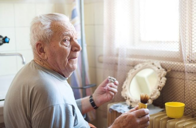 the lost art of shaving - old man shaving with a badger brush and safety razor